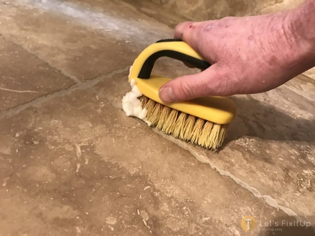 scrubbing grout with baking soda paste