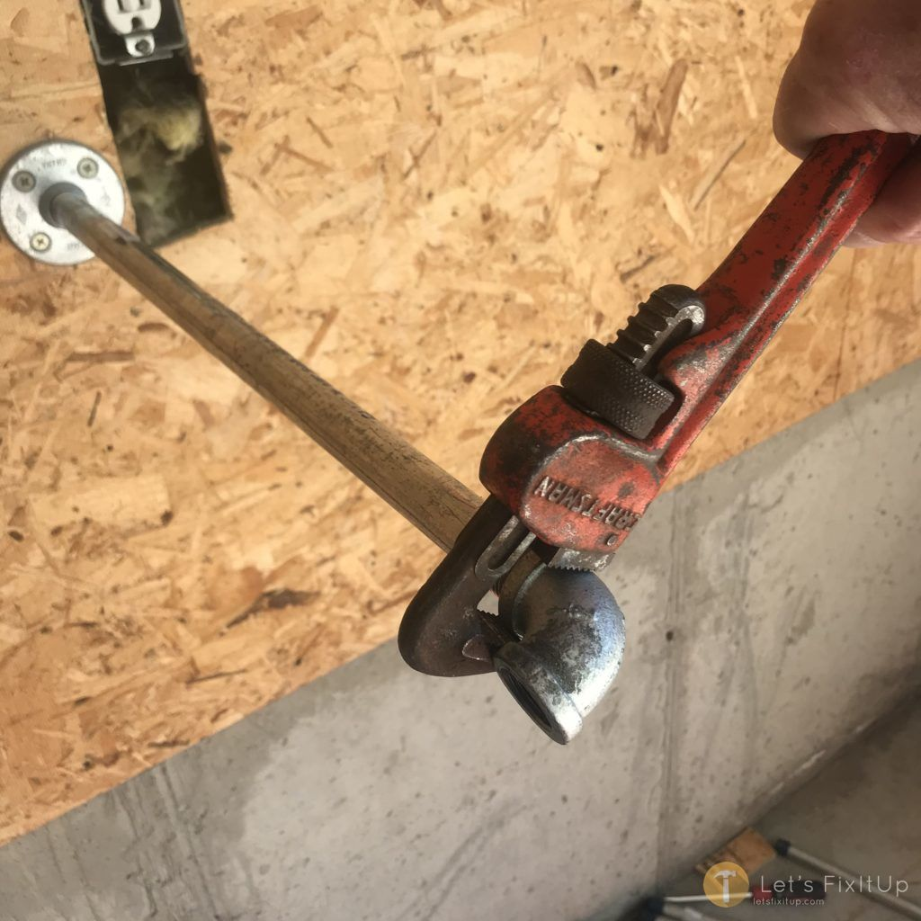 Tightening the fittings onto the pipe with a pipe wrench